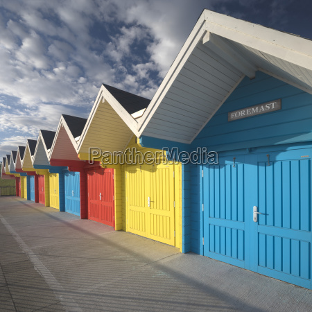 row of colourful beach huts lit