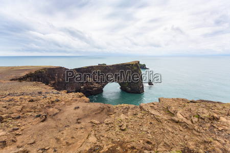 lava arch on dyrholaey promontory in