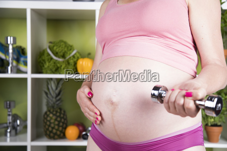 pregnant fitness woman with dumbbells